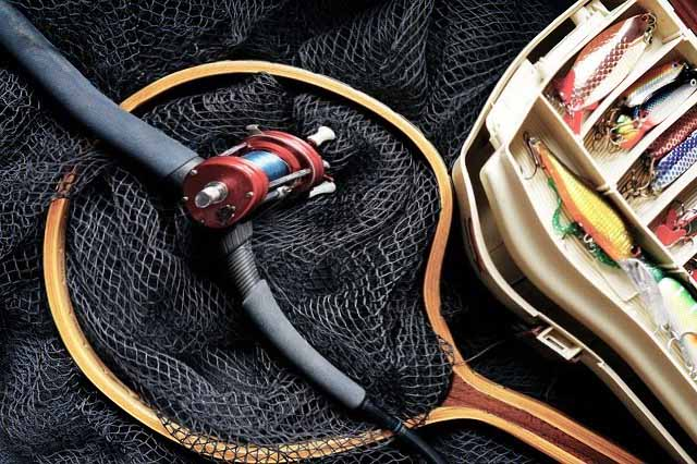 des accessoires de pêches : canne à pêche, epuisette et boite de leurres