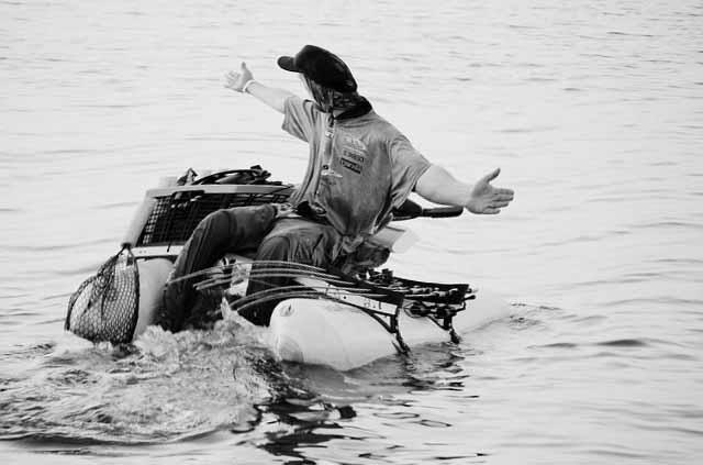 un pêcheur qui pêche avec sa canne à pêche sur un float tube